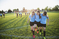 Middle school girl soccer players helping injured teammate off field - HEROF13389
