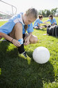 Middle school girl soccer player adjusting shin guard on field - HEROF13392