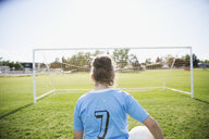 Middle school girl soccer player with soccer ball facing goal net on sunny field - HEROF13395