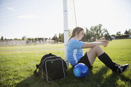 Middle school girl soccer player with duffel bag and soccer ball leaning on goal net post - HEROF13398