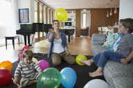 Mother and sons playing with multicolor balloons in living room - HEROF13422