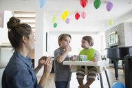 Mother watching sons eating birthday cake - HEROF13425