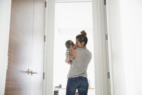 Mother holding baby son in doorway - HEROF13428