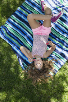 Overhead of girl laying on blanket blowing bubbles in backyard - HEROF13437