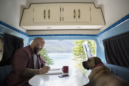 Man with dog writing in journal at table in the back of camper van at lakeside - HEROF13452