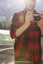 Man using digital camera at sunny lakeside - HEROF13458