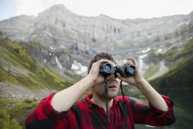 Man using binoculars below remote mountain - HEROF13461 - Hero Images/Westend61