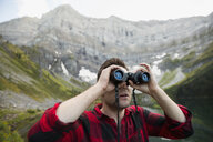 Man using binoculars below remote mountain - HEROF13461