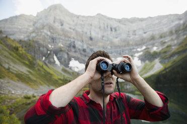 Man using binoculars below remote mountain - HEROF13461
