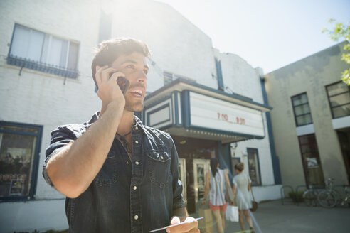 Man talking on cell phone outside sunny movie theater - HEROF13467
