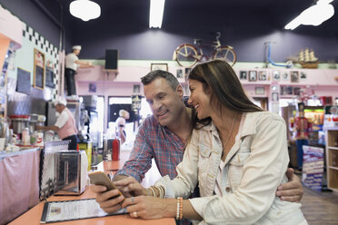 Mature couple using cell phone in soda fountain shop - HEROF13479