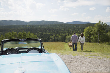 Mature couple with picnic basket walking away from convertible at rural overlook - HEROF13485