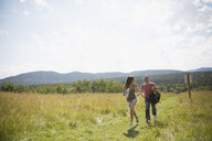Mature couple with backpacking hiking in sunny rural field - HEROF13491