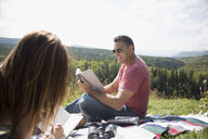 Mature couple reading books on blanket in sunny remote grass - HEROF13494