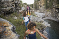 Mother and daughters hiking over rocks above water - HEROF13506