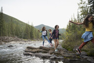 Mother and daughters hiking on rocks along creek - HEROF13515