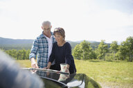 Mature couple looking at map on automobile hood at sunny rural overlook - HEROF13521
