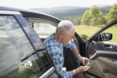 Mature man using cell phone at open car door - HEROF13527