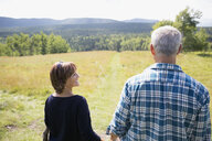 Mature couple walking in sunny remote rural field - HEROF13530