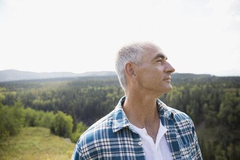 Mature man looking away on remote rural hillside - HEROF13533