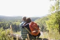 Mature couple with backpack hiking looking at remote sunny rural view from hilltop - HEROF13536