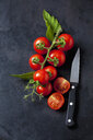 Whole and sliced cherry tomatoes and kitchen knife on dark ground - CSF29217