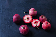 Sliced and whole red-fleshed apples on dark ground - CSF29292