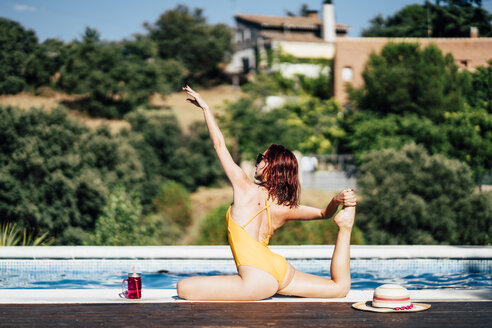 Pretty woman in swimsuit along the edge of pool makes yoga. Spain. - OCMF00248