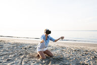 Thailand, woman using virtual reality glasses on the beach in the morning light - HMEF00187