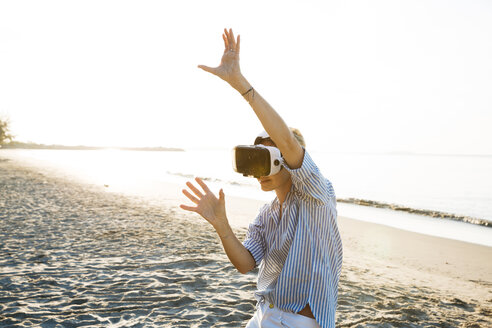 pretty blonde woman using virtual 3D glasses on a beach in Thailand, in the morning light - HMEF00190