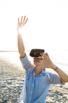 Thailand, woman using virtual reality glasses on the beach in the morning light - HMEF00193