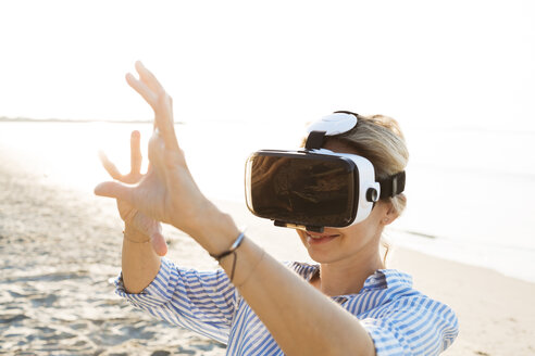 Thailand, woman using virtual reality glasses on the beach in the morning light - HMEF00196