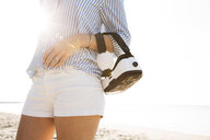 Wman with virtual reality glasses on the arm, at the beach against the sun - HMEF00199