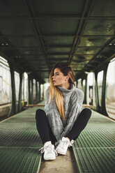 Young woman woman sitting in an abandoned train car - ACPF00403