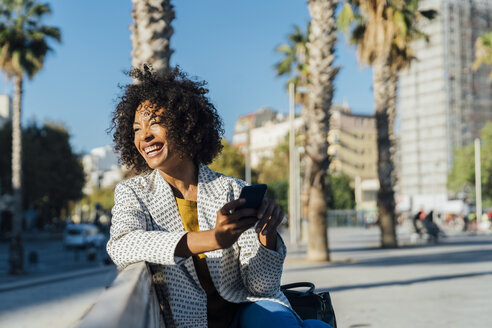 Beautiful woman sitting on a bench in the city, using smartphone - BOYF01321