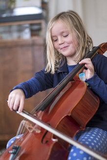 Portrait of smiling blond girl playing cello - HAMF00560