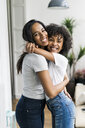Portrait of two happy girlfriends hugging at home - GIOF05637