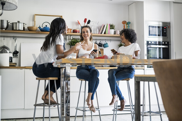 Three happy women sitting at kitchen table at home socializing - GIOF05646