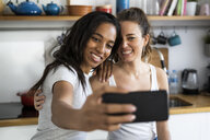 Two happy girlfriends taking a selfie at home - GIOF05649