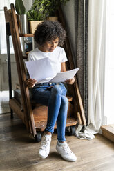 Woman sitting on steps at home looking at document - GIOF05667