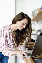 Smiling woman using laptop in kitchen at home - GIOF05679