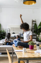 Cheering woman using tablet on table at home with friends in background - GIOF05685