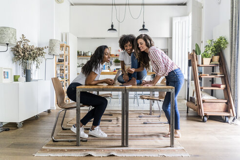 Three happy women with digital devices on table at home - GIOF05688