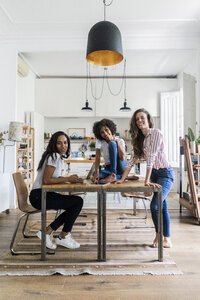 Portrait of three happy women at table at home - GIOF05691