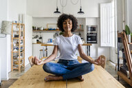 Smiling woman with closed eyes in yoga pose on table at home - GIOF05697