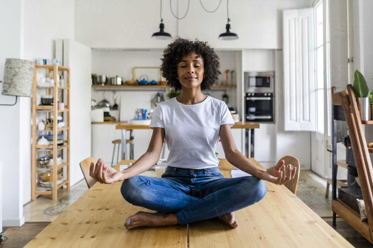 Smiling woman with closed eyes in yoga pose on table at home - GIOF05697 - Giorgio Fochesato/Westend61