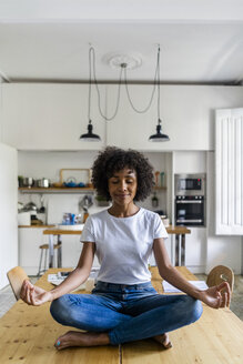 Smiling woman with closed eyes in yoga pose on table at home - GIOF05700