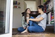 Two girlfriends at home, sitting on floor, talking - MOEF01944