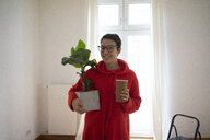 Young woman moving into her new home, carrying a potted plant - MOEF01974