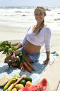 Portrait of smiling pregnant woman on the beach with healthy picnic - ECPF00304